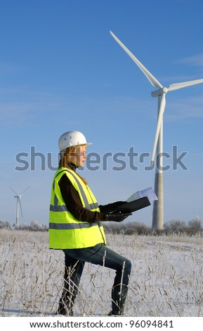 Young architect-woman wearing protective winter cloth standing against wind turbines