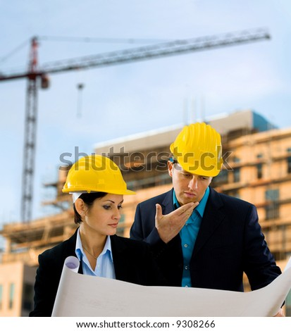 Young architects looking at blueprint in front of construction site, building and crane.