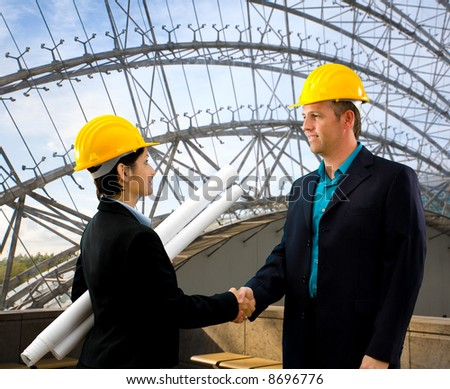 Young architects wearing a protective helmet shaking hands indoor.