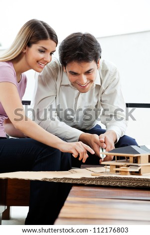 Young architects working on house model project together