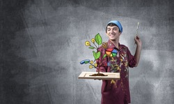 Young artist drawing plant of wealth and business success. Happy painter in dirty shirt and bandana standing on grey wall background. Original business idea generation and development.