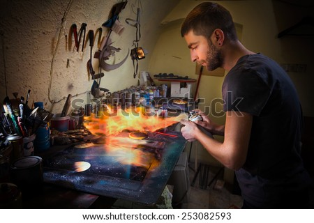 Young artist finishing his artwork with spray paint and fire