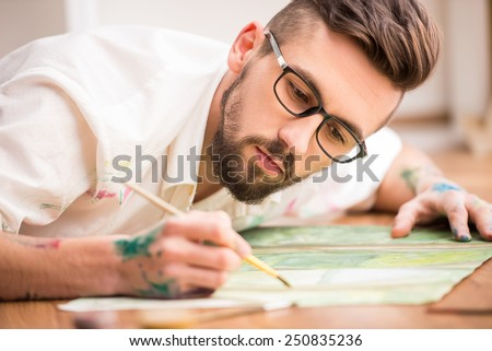 Young artist is painting on canvas is lying on studio floor. Close-up.