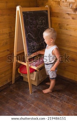 Young artist. Little boy drawing with chalk on a blackboard