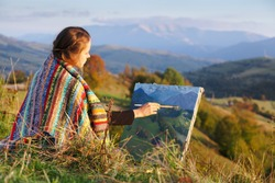 Young artist painting an autumn landscape