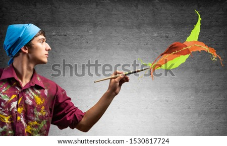 Young artist painting colorful brush strokes. Male painter in dirty shirt and bandana with paintbrush on grey wall background. Creative hobby and artistic occupation. Art classes concept.