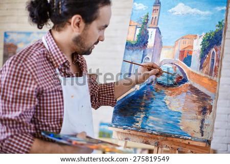 Young artist painting Italian landmark in studio