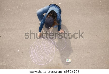 Young artist painting on the street