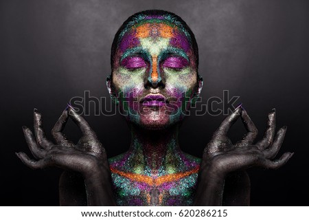 Young artistic woman in black paint and colorful powder. Glowing dark makeup. Creative body art on the theme of space and stars. Bodypainting project: art, beauty, fashion