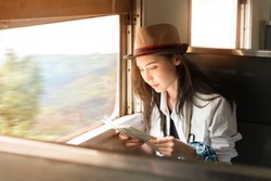 Young Asia backpacker woman travels her journey by train, traveling to countryside in classic train sitting and looking out of a train window,Thailand