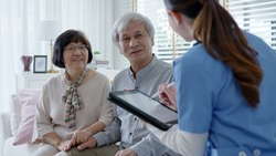 Young asia female nurse, assisted living, in-home carer or doctor visit old senior citizen at home talk about result follow up checklist, health care advice or prescription online on tablet computer.