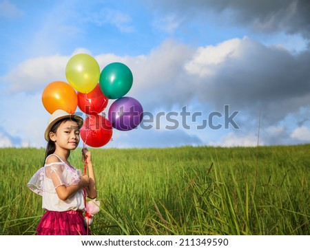 young asia girl holds tightly to a large bunch of helium filled balloons in nature park