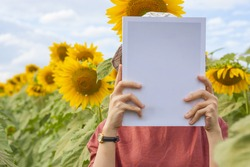 Young Asia girl in the red dress holding book or magazine mock up with sunflowers field background in copy space, people with landscape and outdoor education concept