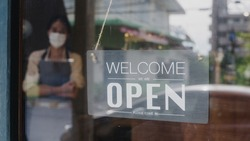Young Asia girl wear face mask turning a sign from closed to open sign on door looking outside waiting for clients after lockdown. Owner small business, food and drink, business reopen again concept.