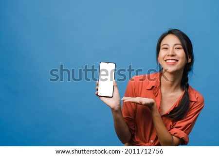 Young Asia lady show empty smartphone screen with positive expression, smiles broadly, dressed in casual clothing feeling happiness on blue background. Mobile phone with white screen in female hand.