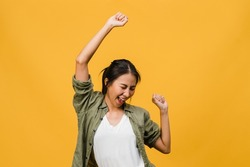 Young Asia lady with positive expression, joyful and exciting, dressed in casual cloth over yellow background with empty space. Happy adorable glad woman rejoices success. Facial expression concept.
