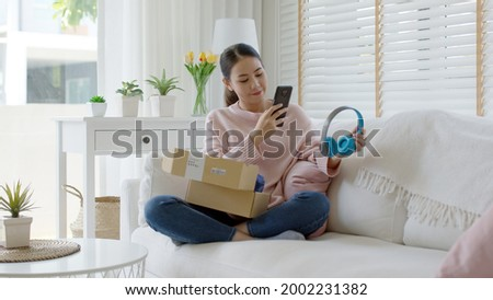 Young asia people happy teen girl smile unbox open gift new headphone buy order from online store shop take photo shoot camera show post social media app blog vlog share sit relax at home sofa couch.