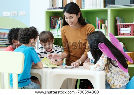 Young asia woman teacher teaching kids in kindergarten classroom, preschool education concept
