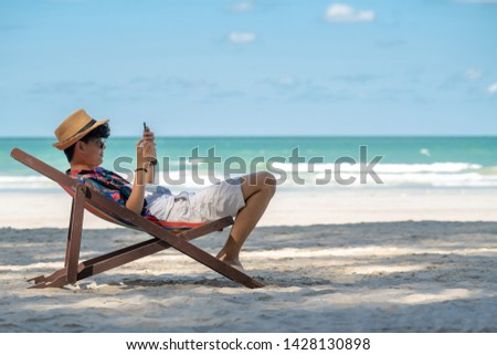 Young asian adult men traveler in casual wear relaxing and lying down on beach chair on tropical island beach in summer holidays vacation travel trip using smartphone for text, selfie or take a photo