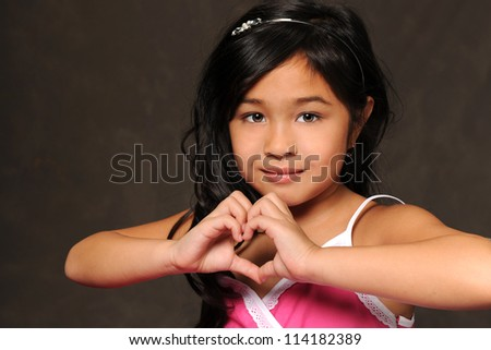 Young Asian American girl making heart with hands