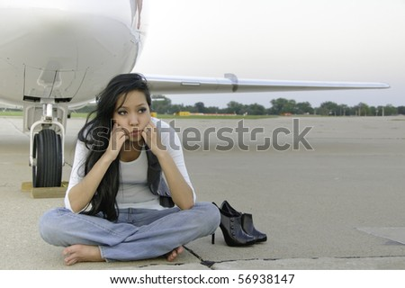 Young Asian-American woman sits waiting by airplane on tarmac