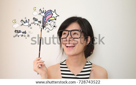 Young asian artist woman wearing glasses  holding pain brush with unicorns and rainbows doodles illustration  - Shutterstock ID 728743522