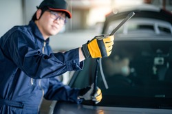 Young Asian auto mechanic checking windshield wiper in auto service garage. Mechanical maintenance engineer working in automotive industry. Automobile servicing and repair