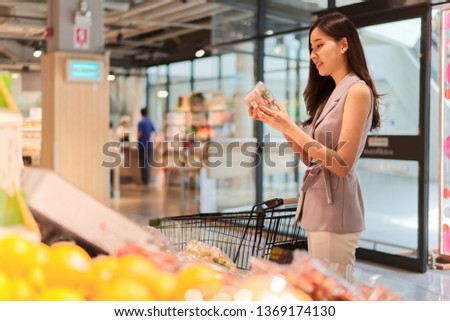 Young Asian beautiful girl is choosing fruits in supermarket. She is holding and looking a quality of strawberry in a box. She buying daily products for good heath. Healthcare concept.