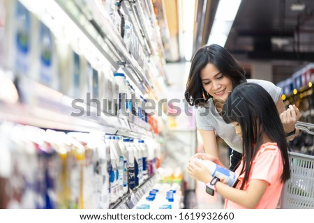 Young Asian beautiful mother holding grocery basket with her child walking in supermarket. She is choosing daily milk product picking up from shelf with her little daughter. Shopping for healthy.