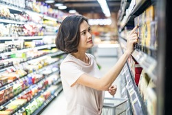 Young Asian beautiful woman holding grocery basket walking in supermarket. She is looking and choosing things to buy with smile. Seen from side while she looking on product. Shopping concept.