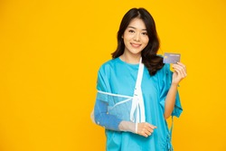 Young Asian beautiful woman wearing patient outfits and put on a soft splint due to a broken arm and holding credit card isolated on yellow background, Personal accident concept
