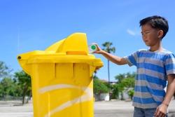 Young Asian boy drop a plastic water bottle in a yellow bin.