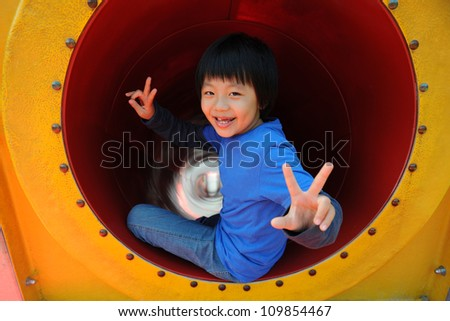 Young Asian boy having fun on playground (slide)