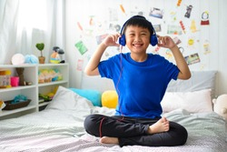 Young asian boy is smiling and listening to music