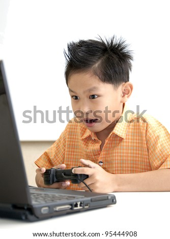 Young Asian boy plays the game with black laptop computer
