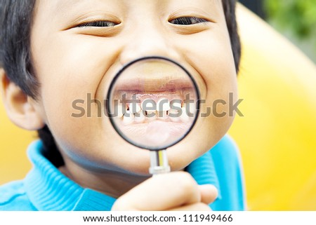Young asian boy showing his healthy teeth through hand magnifier