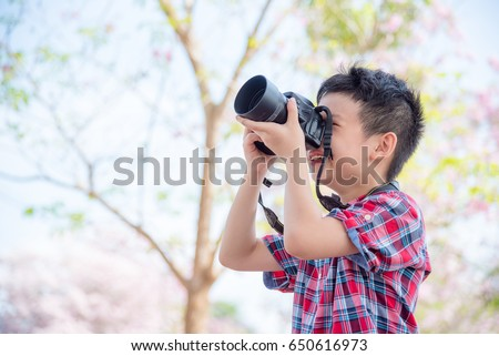 Young asian boy taking photo by camera in park