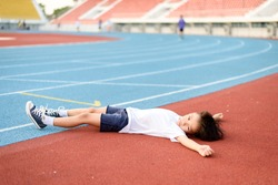 Young Asian boy tired and lay down on the running track.