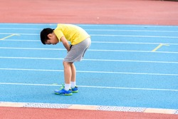 Young Asian boy tired on blue track after running in the stadium during day time to practice himself.