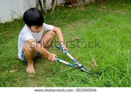 Young asian boy use hand grass scissors to cut the long grass at home garden with tired and boring face.