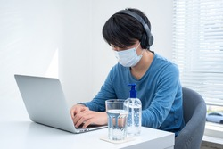 Young Asian boy wearing face mask working on laptop during coronavirus pandemic