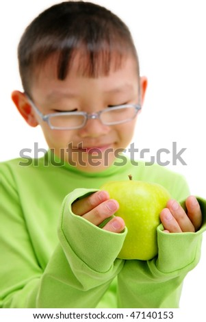 young asian boy with a big green apple