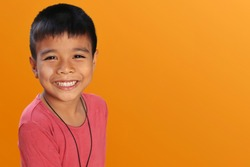 Young Asian boy with black skin  standing and smiling, saw the teeth in his happy face and looked at the camera  Isolated orange background