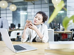 young asian business executive sitting at desk in office playing with mobile phone.