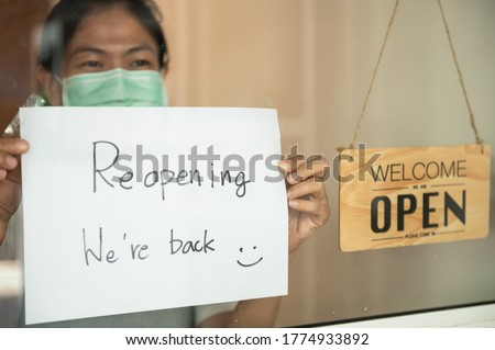 Young Asian business owner coffee shop manager wearing face surgical mask attaching reopen sign for announcing shop reopening after be closed due to business crisis from coronavirus outbreak problem.