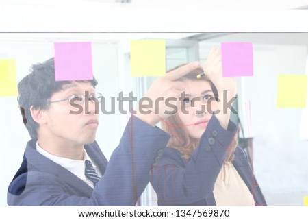 Young Asian business people use post it notes on glass wall to share idea at meeting room. Teamwork and brainstorm concept.