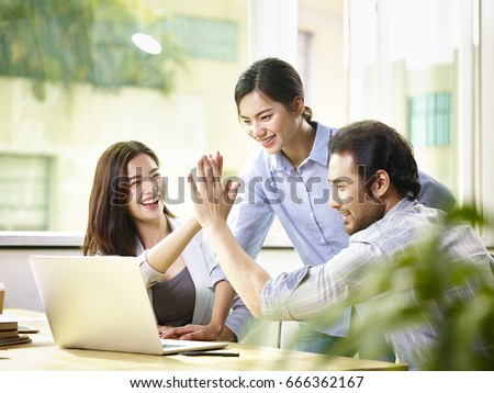young asian business person giving coworker high five in office celebrating achievement and success. #666362167