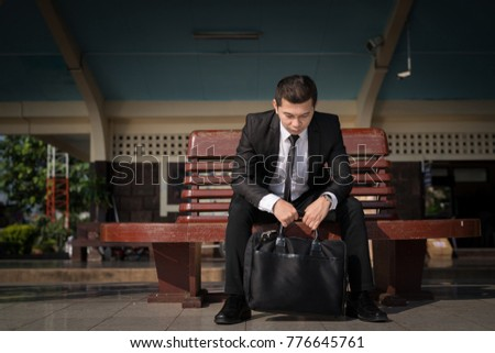 Young asian businessman feel stressed/worry/headache/disappoint during working while sit at train station,hand holding Laptop bag