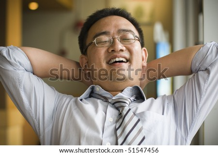 young asian businessman is daydreaming and looks happy. - stock photo