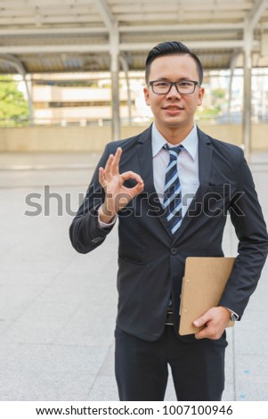 Young Asian businessman is showing OK sign. #1007100946